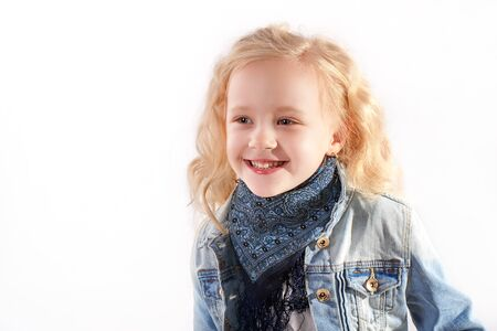 tied girl: Little girl in a blue denim jacket is smiling. On the neck of the girl tied around a blue scarf