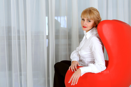 Business Woman In Formal Clothes Sitting In A Red Chair In A Half Turn  Against