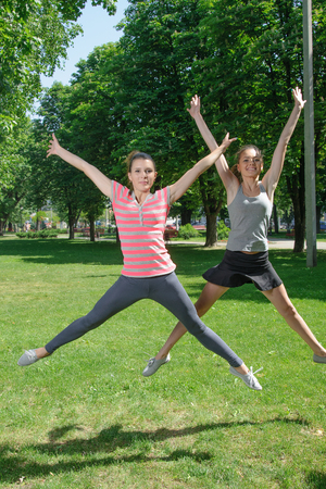 synchronous: Two girls doing sport exercises in the form of synchronous jumps up on outdoors