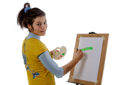 half turn: Girl artist draws on her the easel standing in half turn against an isolated background