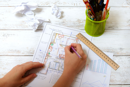 feng shui: The woman draws a diagram of Feng Shui in the apartment layout. View from the top. Stock Photo