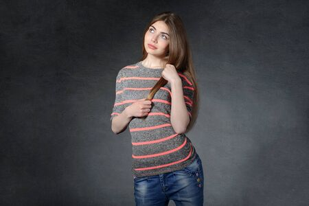 caring for: Girl looking up caring for her hair against dark background Stock Photo