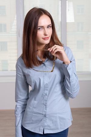formal attire: Girl in formal attire took off her glasses looking at camera