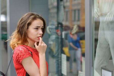 Problem of choice, difficulty, doubt concept. The girl in a red blouse standing near storefront pensively