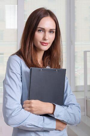 formal attire: Girl in formal attire holding a folder for documents