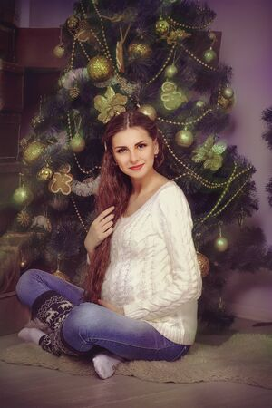 girl socks: Pregnant girl in a sweater and socks sits amid Christmas trees