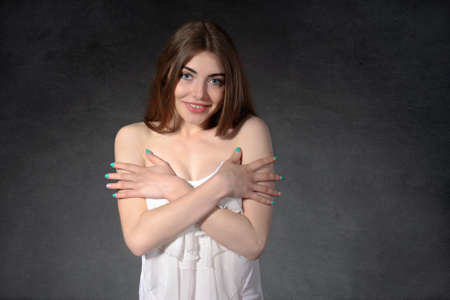 shyness: Concept human emotions. Woman shows shyness and that she was not dressed against the dark background