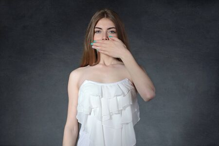 reluctance: Secrecy, reluctance, indifference concept. Woman closed her mouth with her hands against a dark gray background Stock Photo