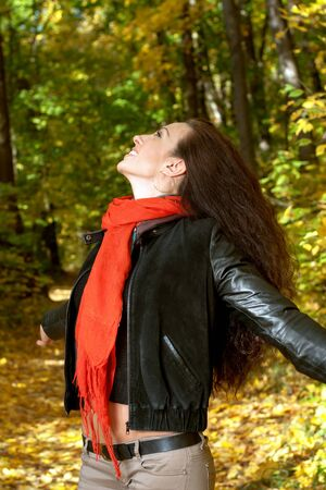 red scarf: Girl in a red scarf catches hands with yellow leaves Stock Photo
