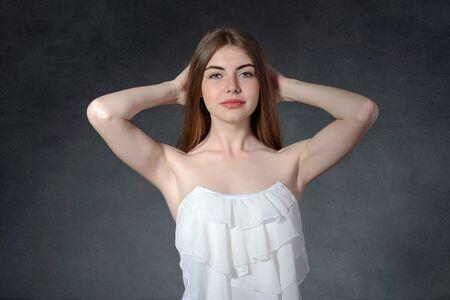 cansancio: Calma, la pereza, el concepto de cansancio. Mujer levant� los brazos extendidos hacia arriba contra un fondo gris oscuro