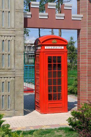 cabina telefono: Cabina de teléfono roja en un parque de la ciudad