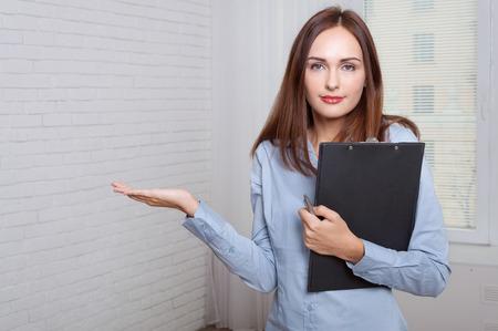 formal attire: Girl in formal attire holding a folder expressing bewilderment