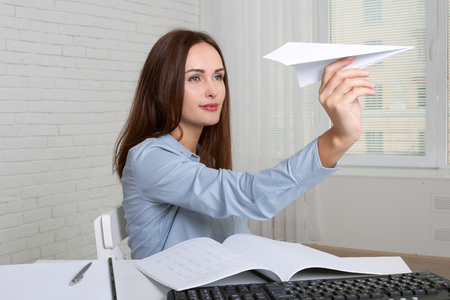 Girl sitting at table in office throwing paper airplane Stock Photo