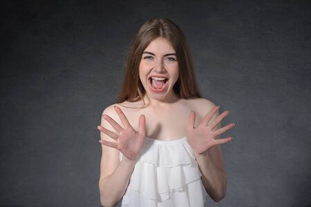 revulsion: Scream, disgust, revulsion concept. Woman is closed from danger against a dark gray background