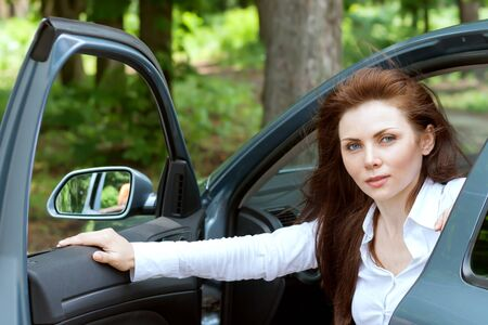 exiting: Beautiful girl opens the door exiting the car