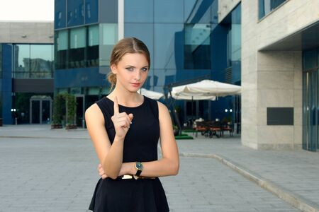 formal dress: Business woman in formal dress showing gesture warnings against the facade of a modern building