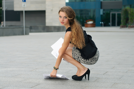 Women fell to the ground documents and she sat down to pick them up Stock Photo - 44012059