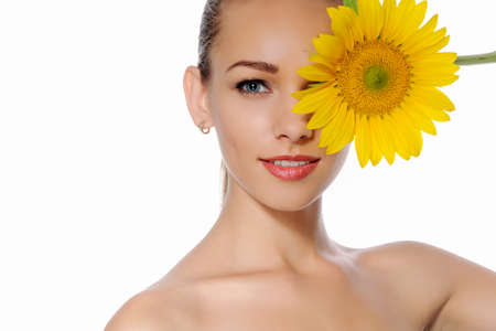 one eye closed: Close-up portrait of a beautiful young, fresh, healthy woman with perfect skin. She closed one eye yellow flower of a sunflower against a background isolated