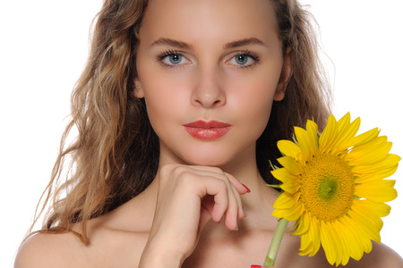 niñas sonriendo: Rich close-up portrait of a beautiful girl with perfect clean skin with sunflower in her hand isolated on white