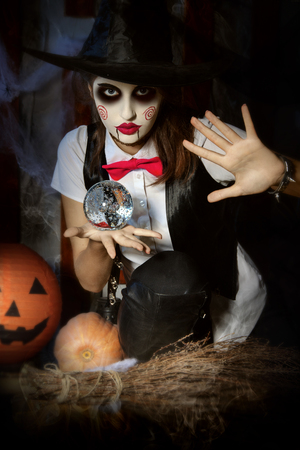 foretell: Halloween, mysticism, magic, mystery. Makeup in the style of Billy doll. Girl witch holding a magic ball transparent and casts a spell over him.