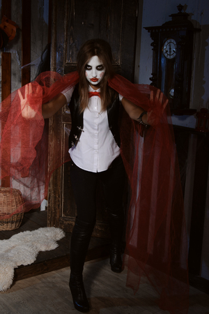 mysticism: Halloween, mysticism, magic, mystery. Makeup in the style of Billy doll. Witch in a red cape makes magical passes Stock Photo