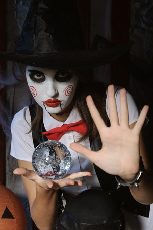 mysticism: Halloween, mysticism, magic, mystery. Makeup in the style of Billy doll. The girl in a magic hat holding a ball Stock Photo