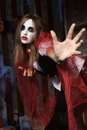mysticism: Halloween, mysticism, magic, mystery. Makeup in the style of Billy doll. Witch in the throes of pulling forward open palm.