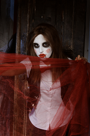 psychic: Halloween, mysticism, magic, mystery. Makeup in the style of Billy doll. Witch stretches red transparent fabric. Stock Photo