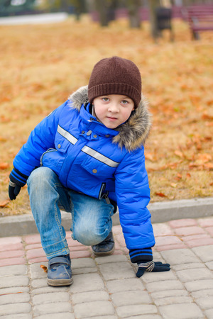 crouched: Boy in blue jacket, crouched down against the backdrop of yellow foliage Stock Photo