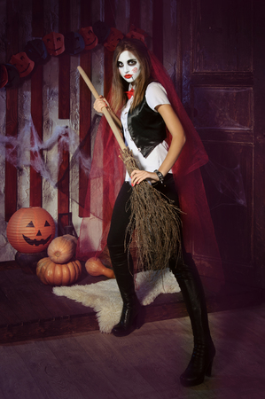 mysticism: Halloween, mysticism, magic, mystery. Makeup in the style of Billy doll. Witch in a red cloak holding a broom