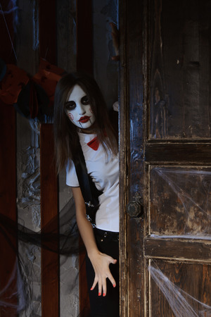 esoterism: Halloween, mysticism, magic, mystery. Makeup in the style of Billy doll. Girl in makeup looks from behind the door