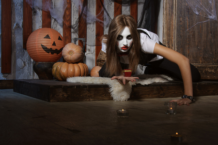 mysticism: Halloween, mysticism, magic, mystery. Makeup in the style of Billy doll. Witch crawling on the floor among the candles