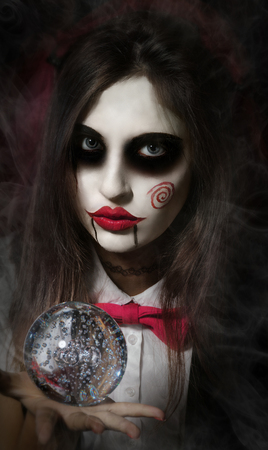 mysticism: Halloween, mysticism, magic, mystery. Makeup in the style of Billy doll. Girl witch holding a magic transparent sphere. Stock Photo