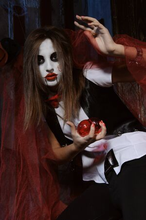 esoterism: Halloween, mysticism, magic, mystery. Makeup in the style of Billy doll. Witch holding a heart