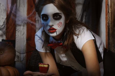 mysticism: Halloween, mysticism, magic, mystery. Makeup in the style of Billy doll. Witch holding a candle