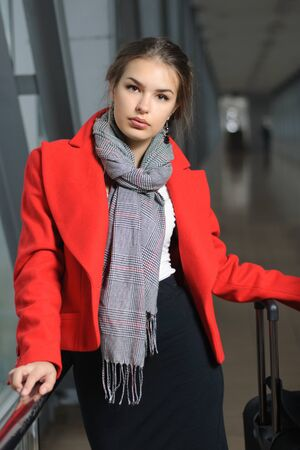 transition: Girl in a red jacket and a gray scarf around her neck with a suitcase standing in the transition from metal structures