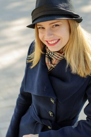 cheerfully: Girl in a hat with a golden hair cheerfully laughs against a blurred background
