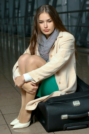 hugging knees: Girl sits on the big suitcase hugging her knees Stock Photo