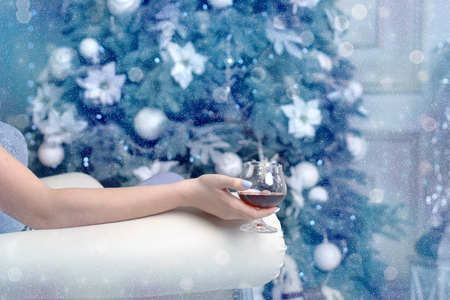 Woman sitting in a chair with a glass of cognac on the background of the Christmas tree
