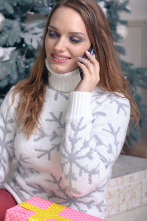 accepts: Girl in a warm sweater speaks on the phone, thanks for the gift and accepts congratulations