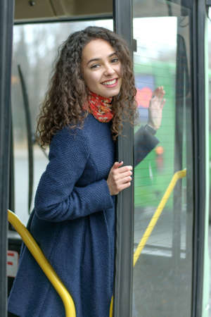 Girl looks out from behind the door of the bus and smiling