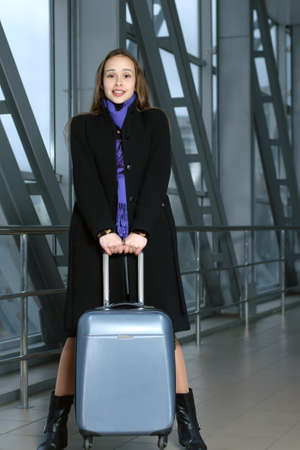 barely: Girl barely raises her suitcase in transit station
