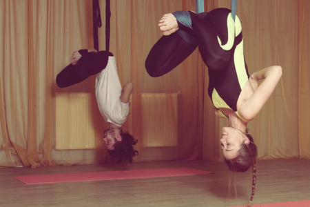 hang body: Classes in yoga fly. The girl and the guy hanging upside down cross their legs and meditate
