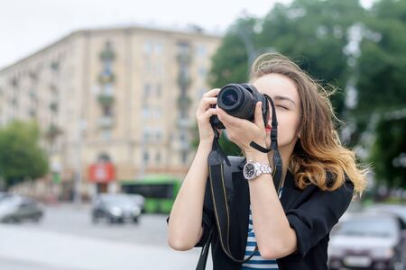 camera girl: Tourists take pictures on her camera against the backdrop of the city Stock Photo