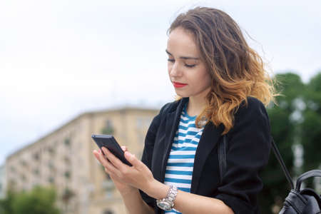communicates: Woman communicates on a mobile phone and smiling at the background of the city Stock Photo