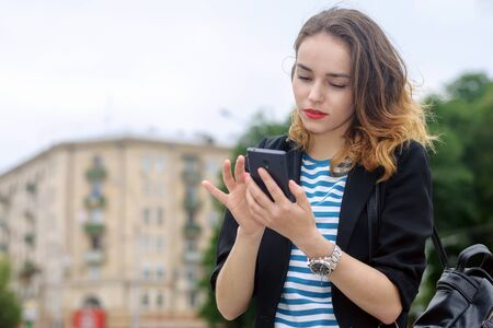 communicates: Girl communicates on a mobile phone and smiling at the background of the city Stock Photo