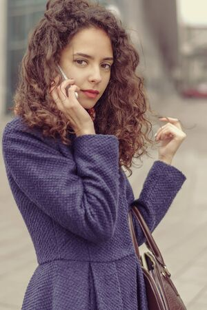 fingering: Girl talking on cell phone and she thoughtfully. She goes through the city and fingering her hair.