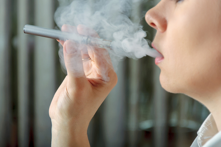 steam mouth: Girl smokes an electronic cigarette and exhaling flavored steam. Concept: safe way of smoking, how to stop smoking