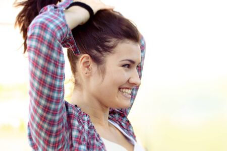 cheerfully: Girl puts her hair and cheerfully laughs against a light background Stock Photo
