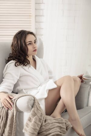 a white robe: Girl sits on the couch and drinking coffee. She is at home, and dressed in a white robe. Concept: lifestyle, health and beauty.